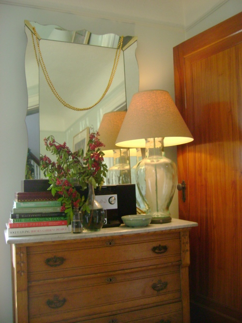 A dresser from Maine loaded up with favourite books, blooms and our stereo