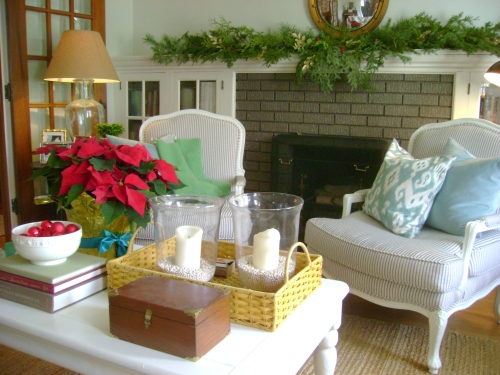 The mantle covered with fresh boughs and poinsettia on the painted coffee table
