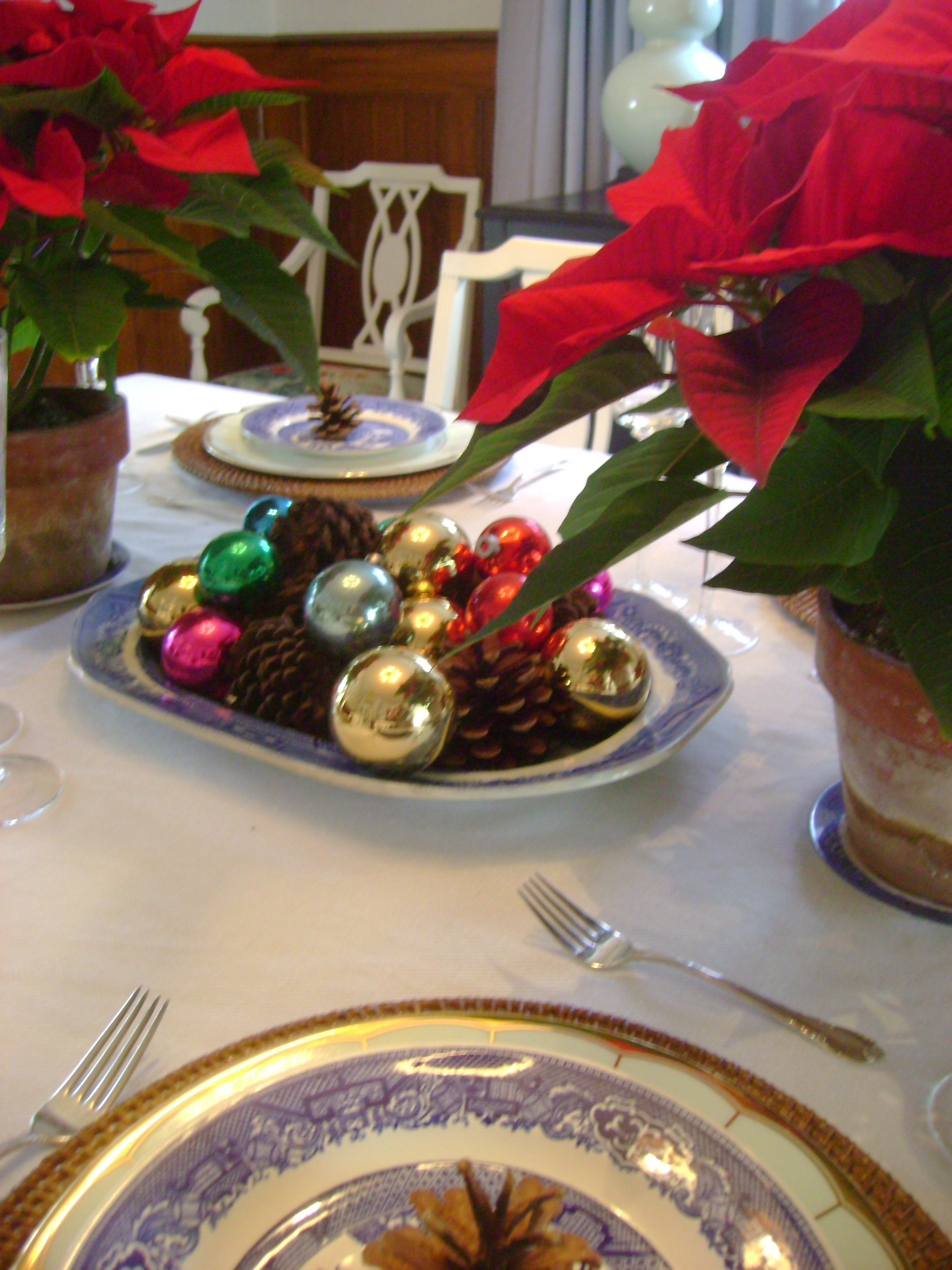 Vintage ornaments, pinecones and an antique patter decorate the table